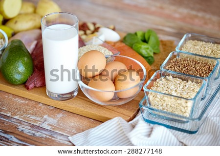 balanced diet, cooking, culinary and food concept - close up of eggs, cereals and milk glass on wooden table - stock photo