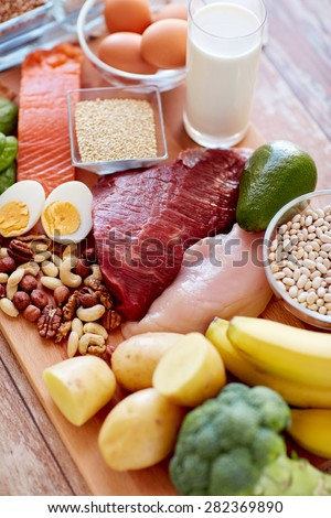 balanced diet, cooking, culinary and food concept - close up of vegetables, fruits and meat on wooden table - stock photo