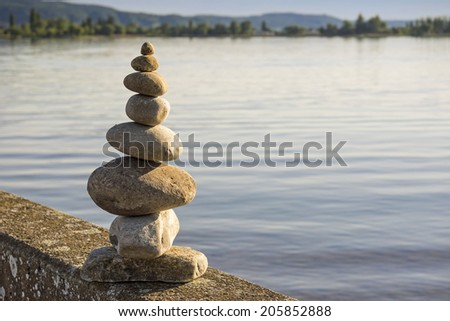 Balanced pebbles stack on sea shore. Lit by warm afternoon sunlight. Shallow depth of field. - stock photo