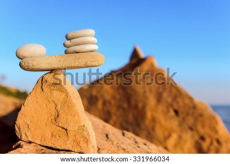 Balanced stack of pebbles on the stony seashore - stock photo