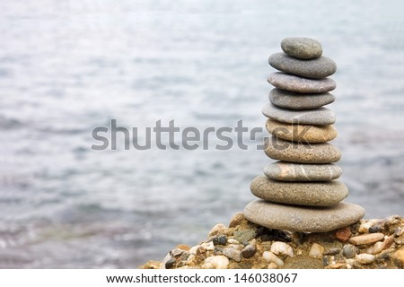 Balanced stack of stones against sea background