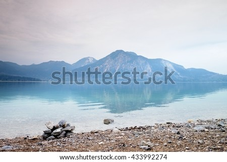 Balanced stone pyramide on shore of blue water of mountain lake. Blue mountains in water level mirror.  Poor lighting conditions.  - stock photo