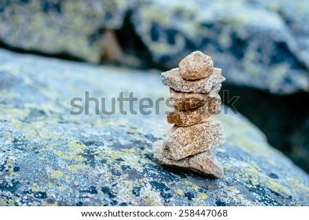 Balanced stone tower. Stability stack. Zen. Rocks around.  - stock photo