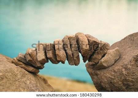 balanced stones in a riverbank - stock photo