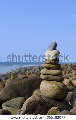 Balanced stones stacked up on top of each other by beach. Shallow focus on stones. Composition sorrounded by rocks and stones on the beach and ocean and blue sky in background.