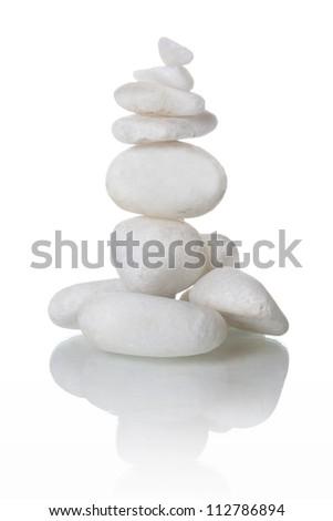 Balanced white stones on white background - stock photo