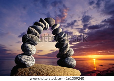 Balancing of pebbles on the boulder in the evening - stock photo
