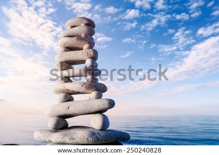 Balancing of stones each other on sky background at the sea - stock photo