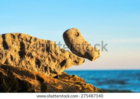 Balancing of stones on the boulder at the seashore - stock photo