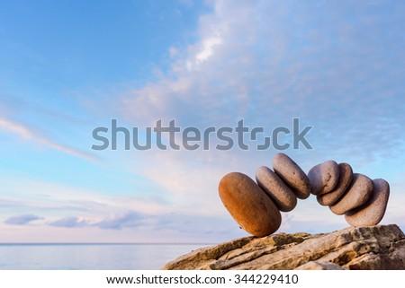 Balancing some of pebbles on the seashore - stock photo