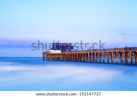 Balboa pier in Newport Beach, California during sunrise shows the wood structure of the pier and a vibrant, blue sky and seascape.  Image shot in slow motion to capture the unique water texture.
