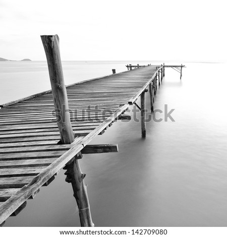 balck and white picture of old bridge to the sea. - stock photo