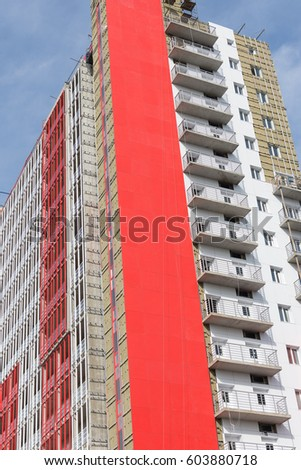 Balconies of a modern building. Red wall