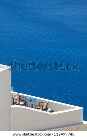 Balcony of a hotel with chairs and table. Beautiful view at the seaside. Santorini, Greece. - stock photo