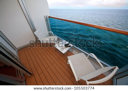 balcony with chairs table bottle glass binoculars on ship with view on sea - stock photo