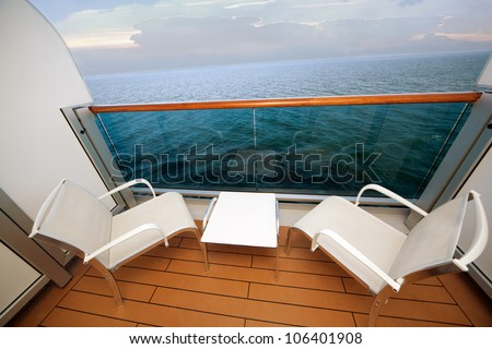 balcony with chairs table on ship with view on sea - stock photo