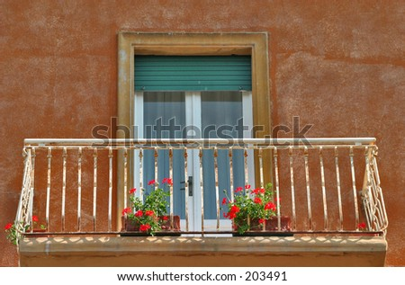 Balcony with double doors and flower pots in Florence, Italy - stock photo