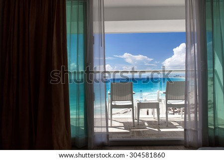 Balcony with plastic bottle of water on wicker table overlooking an ocean - stock photo