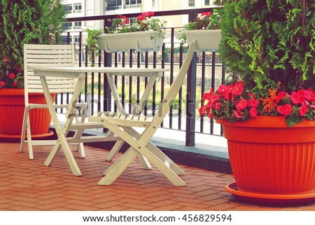 Balcony With Wooden Furniture And Decorative Small Garden. Flowerpots On The Floor And Hanging On Handrail