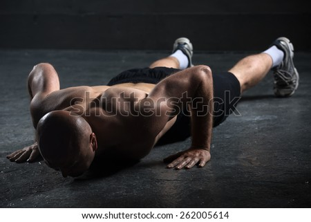 Bald athlete with a beautiful body and a naked torso doing push-ups exercise on the floor. Studio shot in a dark tone. - stock photo