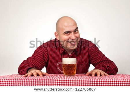 Bald beer drinker sitting in the bar with a glass of cold lager on the table.