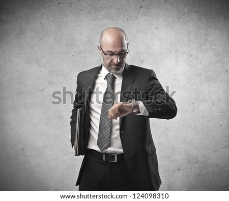 Bald businessman checking the time on his watch - stock photo