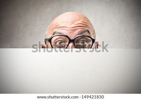 bald businessman hiding behind billboard - stock photo