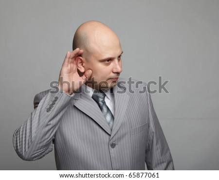 Bald businessman in a gray suit with a gray background. Funny business