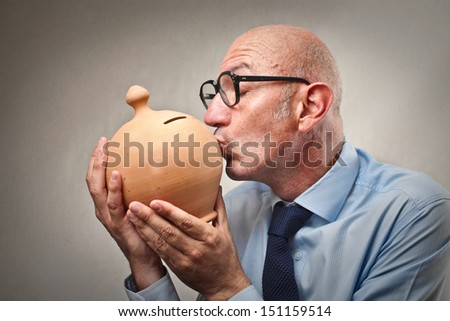 bald businessman kissing piggy bank - stock photo