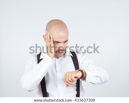 Bald businessman looks at his watch and is late. - stock photo