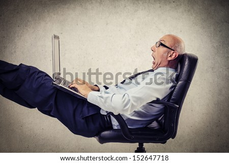 bald businessman relaxing at the office with computer on his legs - stock photo