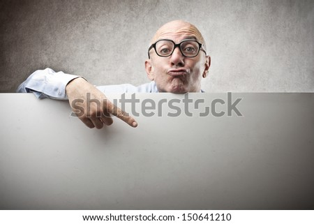 bald businessman shows with finger on blank billboard - stock photo