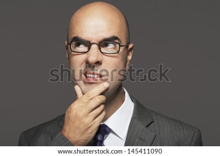 Bald businessman wearing glasses with hand on chin making funny face against gray background - stock photo
