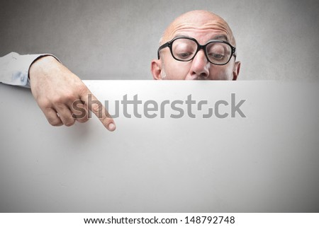 bald businessman with glasses pointing with finger on billboard