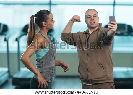 Bald Guy Showing Prety Young Woman How To Take A Selfie With A Cellphone In Fitness Center - Gym In The Background - stock photo