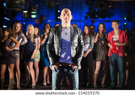 Bald guy with thirteen young people in the background at the club