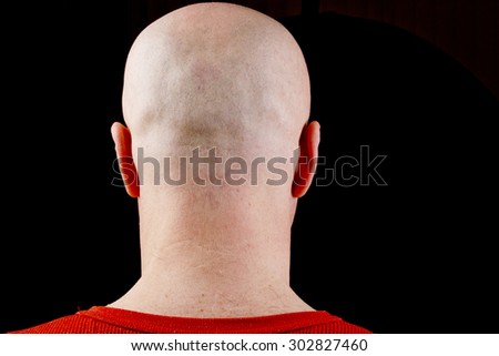 Bald head middle-aged man on a black background. - stock photo