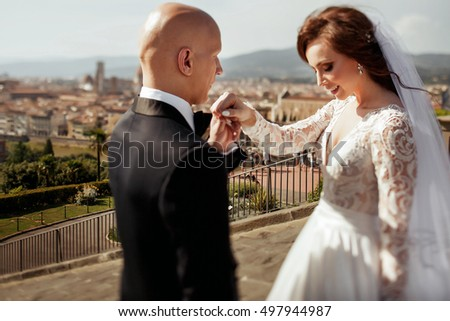 Bald-headed groom looks at shiny bride in marvelous dress
