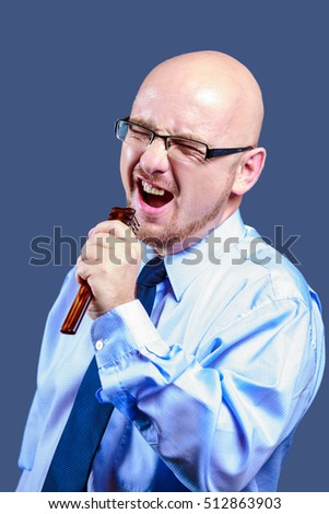Bald headed guy with glasses is singing in a brush