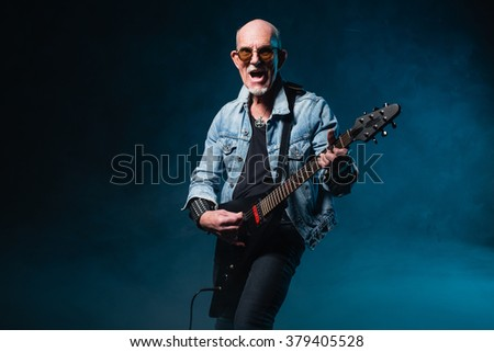Bald heavy metal senior man with electric flying-v guitar in front of dark blue background. - stock photo