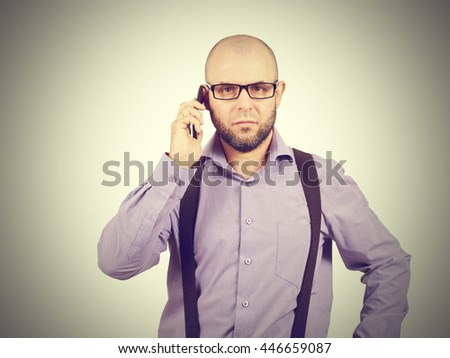 Bald man businessman talking on phone. A bearded man with glasses wearing a shirt with suspenders.
