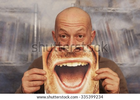 bald man holding a card with a big smile on it - stock photo