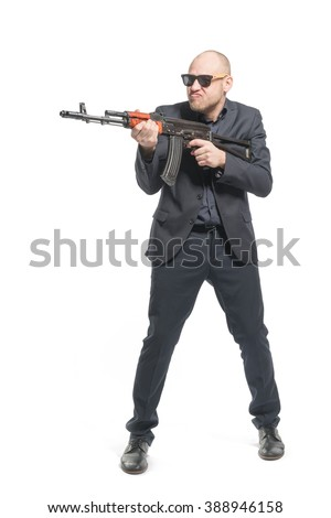 Bald man in a gray suit and sunglasses holding a machine gun in his hands. Isolated - stock photo