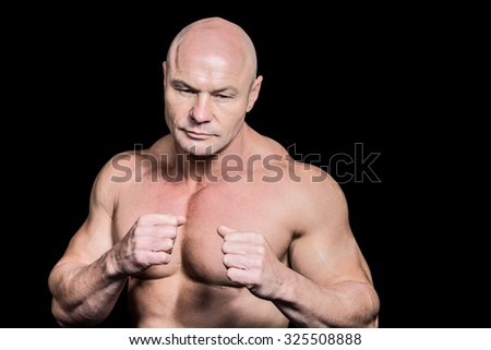 Bald man in boxing pose against black background - stock photo