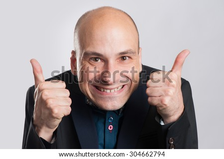 bald man making a silly face and giving thumb up. Isolated on gray.