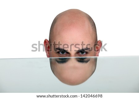 Bald man's head mirrored in a table - stock photo