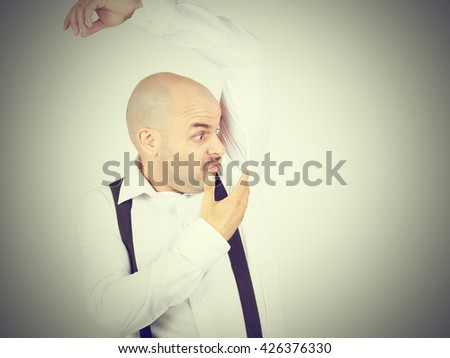 bald man, smelling sniffing his armpit, something stinks bad, foul odor isolated on background. - stock photo