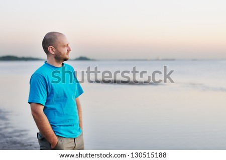 Bald man standing by the sea - stock photo