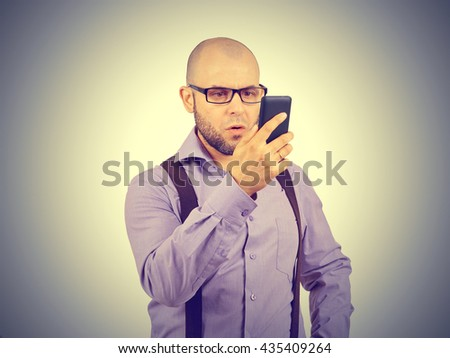 bald man startled looks at the phone.  Human emotion, reaction, expression - stock photo