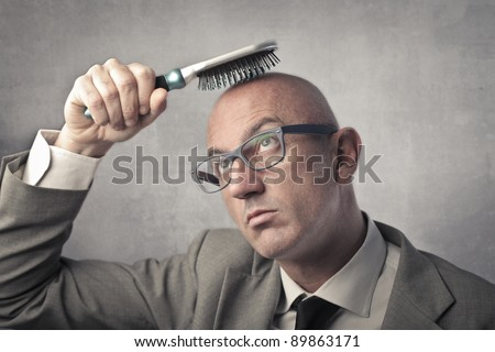 Bald man trying to brush his hair - stock photo